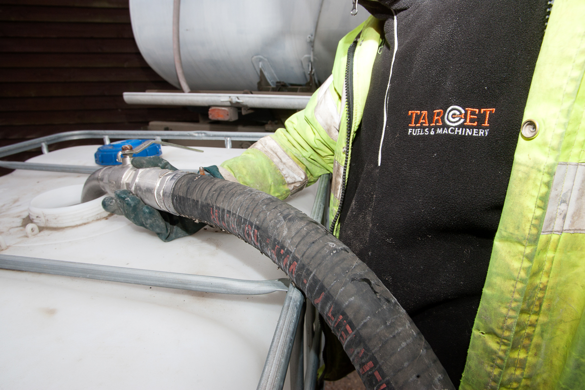 Target Fuels staff using a fuel pump and adding Adblue to a tank in Essex UK